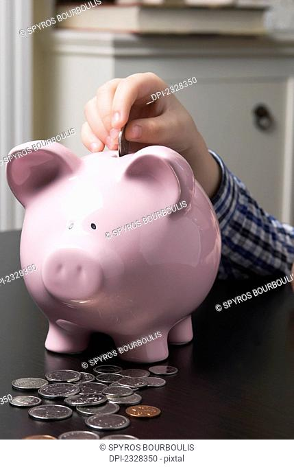 Child Depositing Coins Into A Piggy Bank; Laval, Quebec, Canada