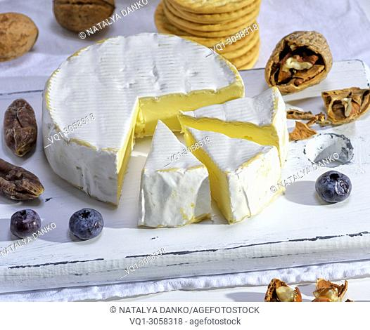 round Camembert cheese on a white wooden board, close up