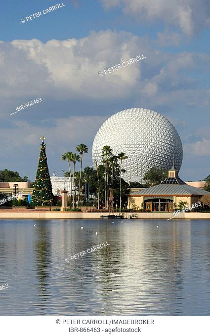 Spaceship Earth and giant Christmas tree as seen across the lake from World Showcase at Epcot, Disney World, Florida, USA