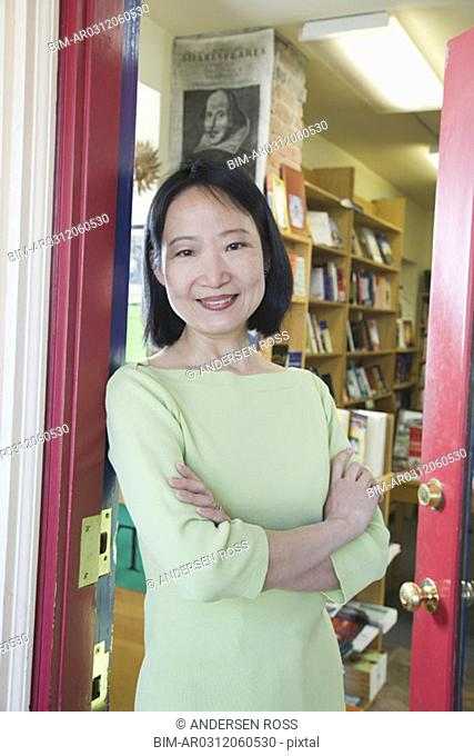 Middle-aged Asian woman in doorway of bookstore