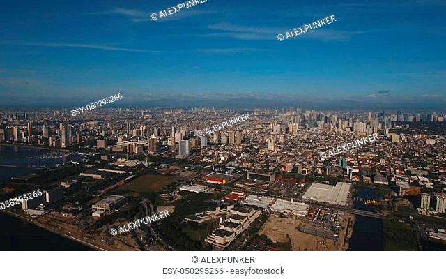 Aerial view skyline of Manila city at sunset. Fly over city with skyscrapers and buildings. Aerial skyline of Manila. Modern city by sea, highway, cars
