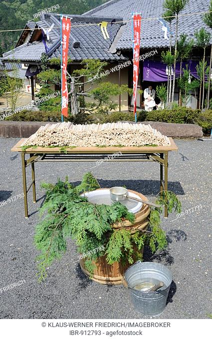 The prayers and wishes of the Yamabushi on wooden sticks placed on a table for later burning, water for controlling the fire, Shogoin Temple near Kyoto, Japan