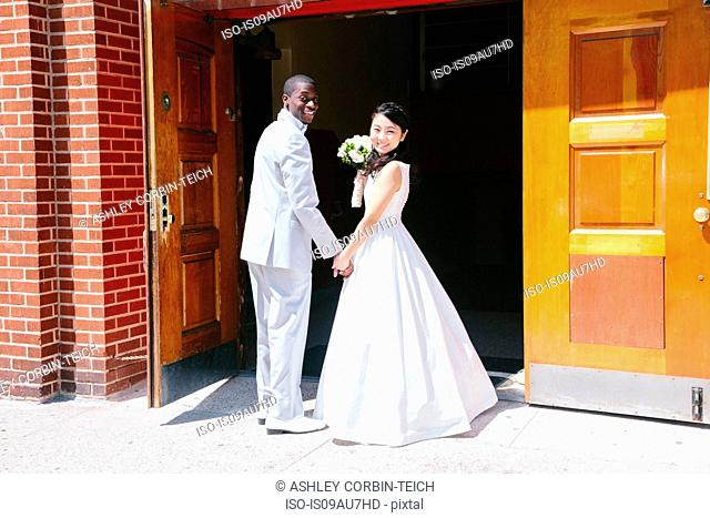 Side view of bride and bridegroom standing at church doors looking at camera smiling