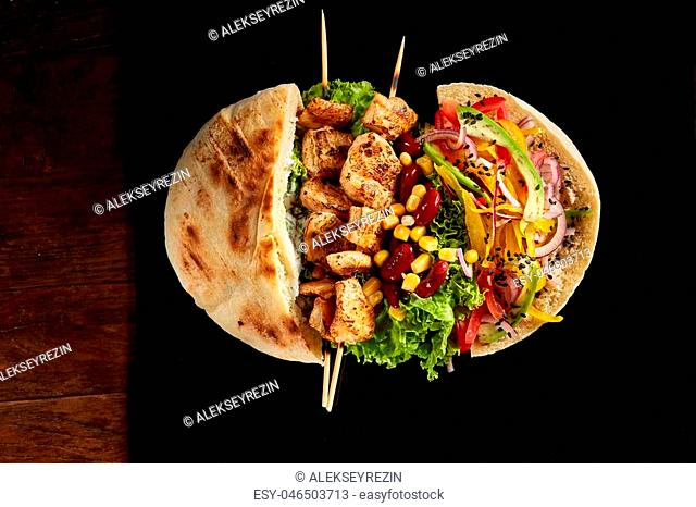 Tasty Jewish pita stuffed with grilled chicken, beans, vegetables, letucce and kebab on black square plate over vintage wooden background, top view, close-up
