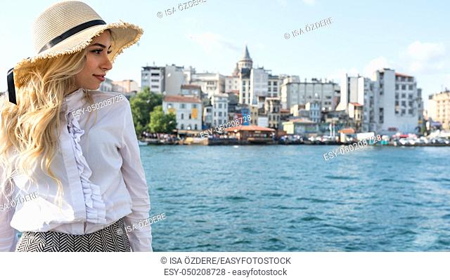 Attractive young beautiful girl stands over Galata Bridge and enjoys view of bosphorus with Galata tower view at background in Istanbul,Turkey