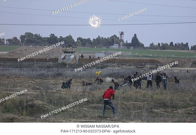 Palestinian protesters run to take cover from tear-gas fired by Israeli troops during clashes following a protest against the decision of US President Trump to...