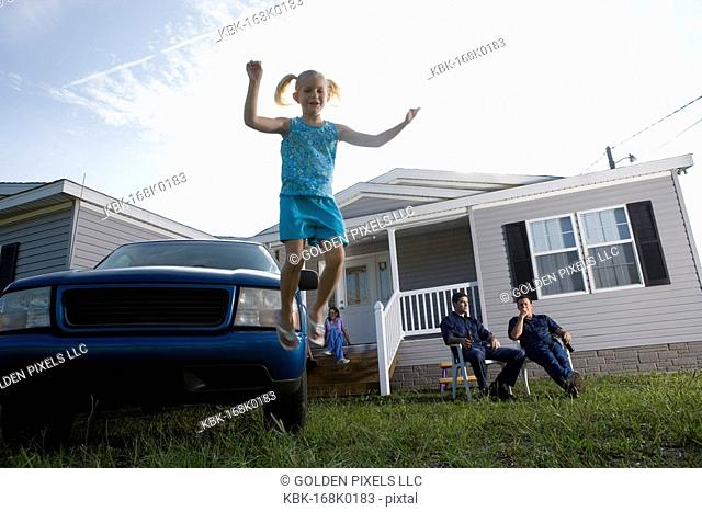 Girl jumping off bumper of old truck parked in front of trailer home, family in background