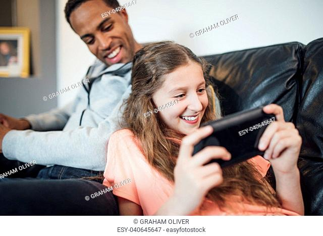 Little girl is playing on a hanheld game console at home and her father is watching her