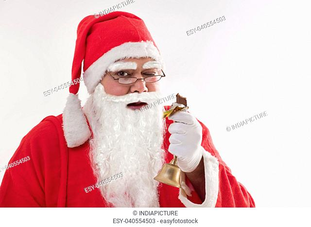 Close-up portrait of Santa Claus winking while eating chocolate bar over colored background