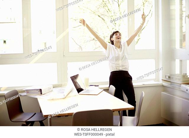 Laughing woman doing stretching exercise in her office
