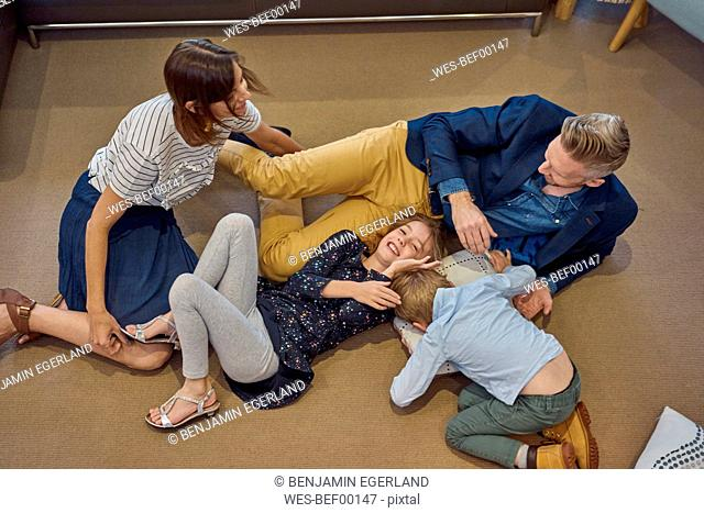 Happy family relaxing on the floor at home
