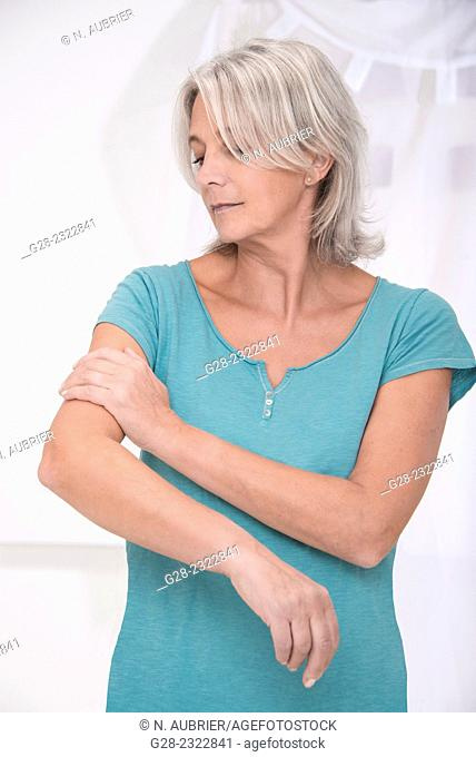 Beautiful mature woman holding her painful or itching arm