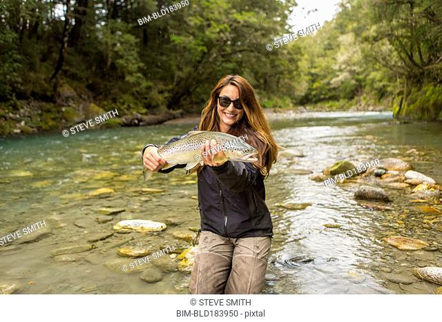 Caucasian woman catching fish in remote river
