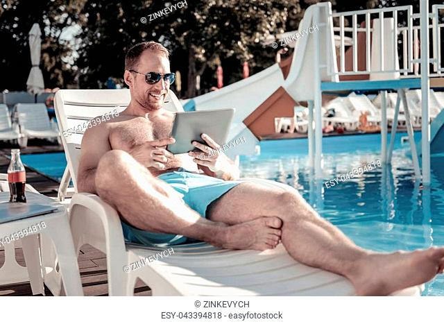Taking a break. Relaxed young guy smiling while lying on a sunbed with a touchpad in his hands and sunbathing next to a swimming pool