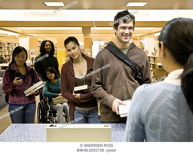 Multi-ethnic people checking out library books