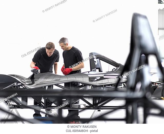 Engineers inspecting carbon fibre car body shell in sports car factory
