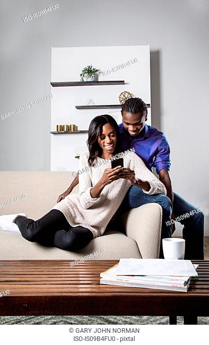 Young couple relaxing on sofa, looking at smartphone