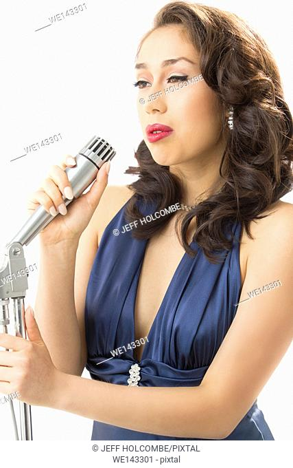 Beautiful young woman singing while holding a microphone, elegant in vintage blue dress, with dreamy look