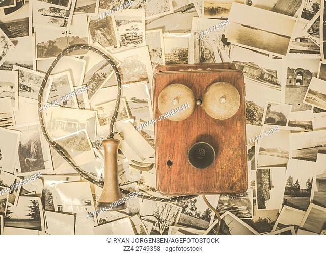 Antique old-fashioned still life on a bell box telephone with candlestick earpiece off the hook laying on vintage photographs. Memory recall