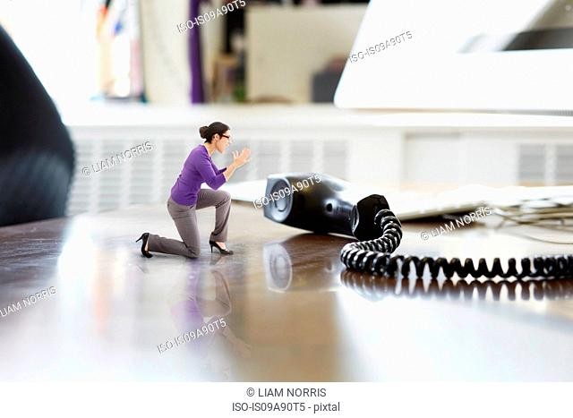 Businesswoman shouting through large telephone receiver on oversized desk