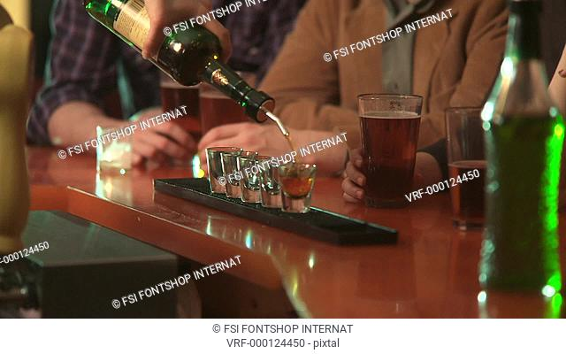 CU, PAN, Selective Focus, A bartender pours liquor into shot glasses and four hands take the drinks