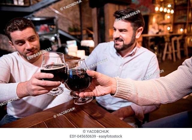 Resting in the pub. Selective focus of glasses with dark beer in hands of happy handsome delighted men while cheering