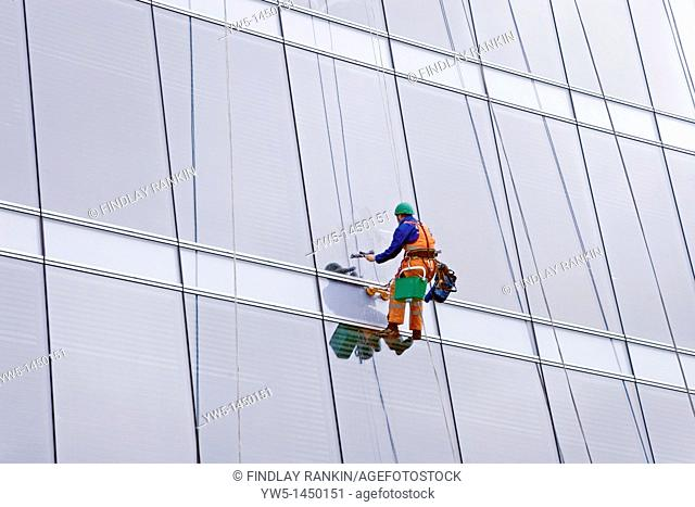 window cleaner suspended on wires at multistorey office block, Glasgow, Scotland, UK, Great Britain