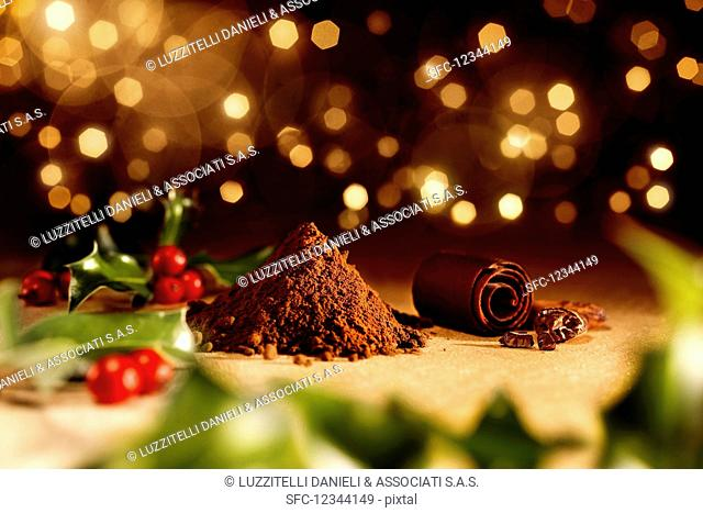 Holly on a wooden table with a pile of cocoa powder, cocoa beans and chocolate rolls (Christmas)