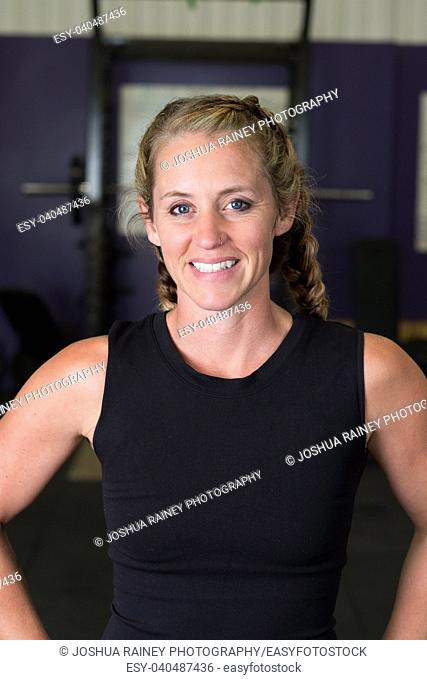 Portrait of a young fit woman during a workout at a crossfit gym focusing on health and fitness for female athletes