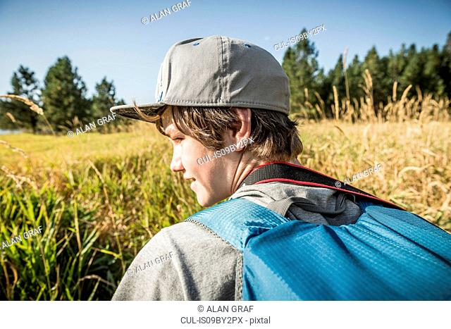 Teenage boy with backpack in field of long grass, Sandpoint, Idaho, USA