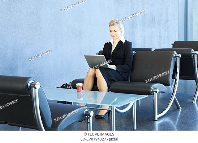 A businesswoman in a waiting room, typing on a laptop