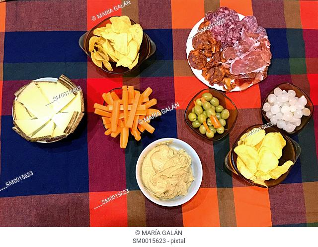 Assorted appetizers: cheese, sausages, chips, carrot sticks, green olives, onions and pate. View from above