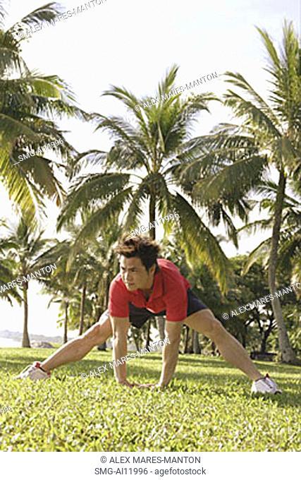 Man doing stretching exercises in park, bending forward