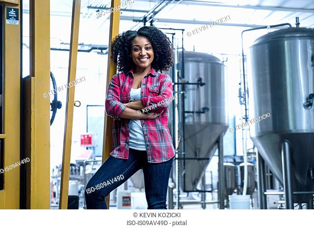 Mid adult woman in brewery leaning against yellow fork lift truck, arms folded looking at camera smiling