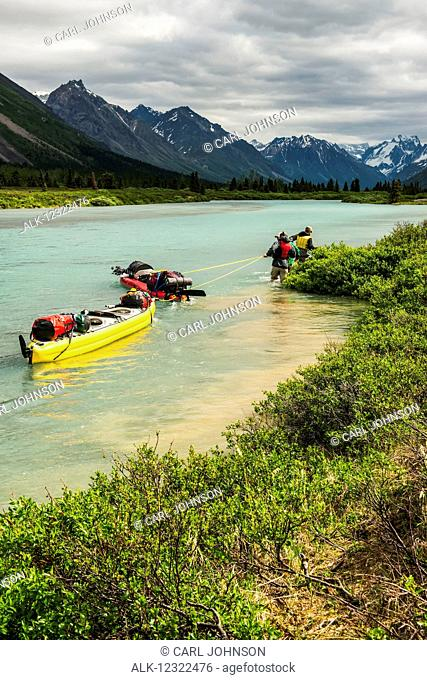 A pair of backcountry travelers line kayaks up a stream in the Twin Lakes area of Lake Clark National Park & Preserve, Southcentral Alaska, USA