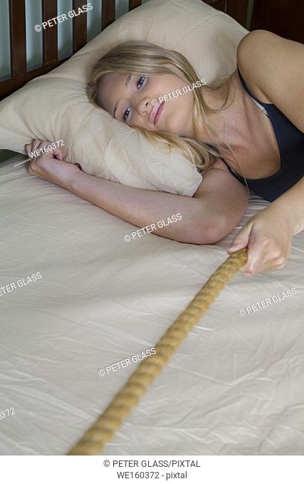 Teenage blonde girl lying in her bed, pulling on a rope