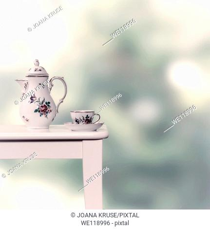vintage tea pot and cup on a white stool