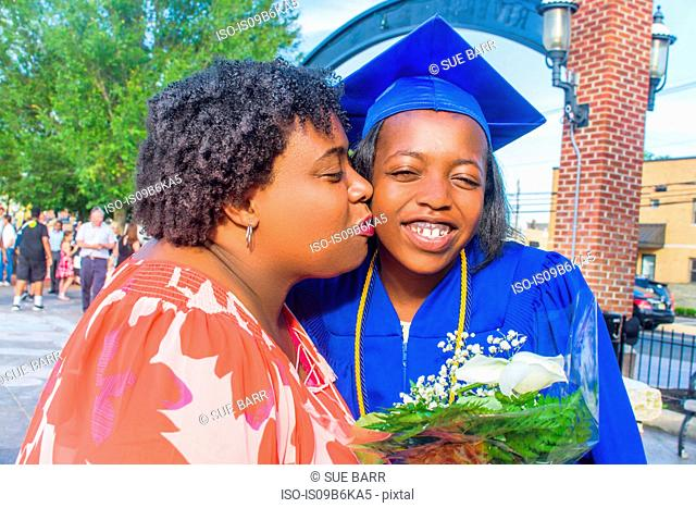 Mother kissing daughter on her graduation day