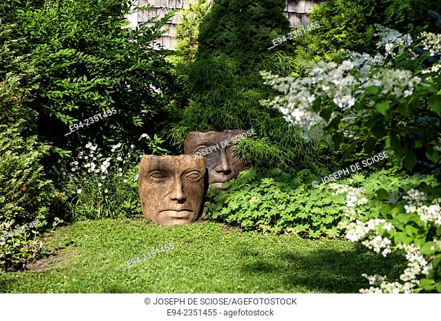 A garden with face statuary in île d'Orléans, Quebec, Canada