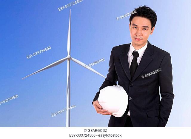 engineer holding white helmet with wind turbine background