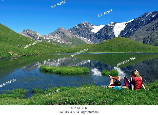 two teens sitting in mountain meadow and enjoying the view to mountain lake, France, Savoie, Sainte-Foy Tarentaise