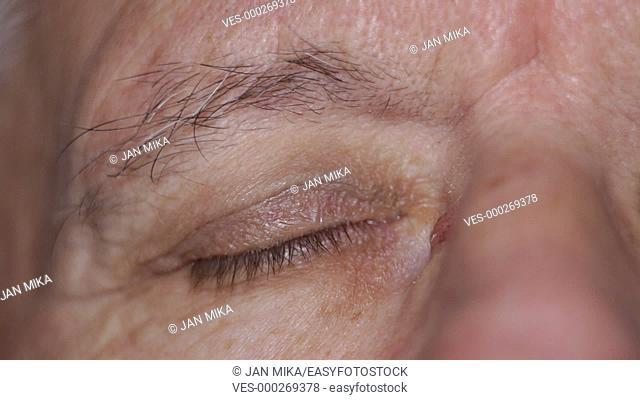 Closeup of senior man opening his eye