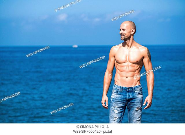 Muscular man standing in front of the sea