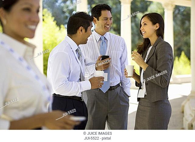 Small group of business colleagues standing in colonnade, holding paper cups, talking, side view