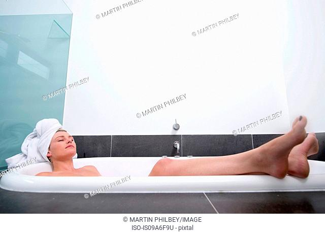 Young woman lying in bath with eyes closed
