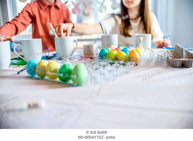 Cropped shot of teenage girl and brother at table dyeing hard boiled eggs for Easter