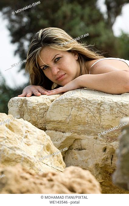 woman leaning on the rocks