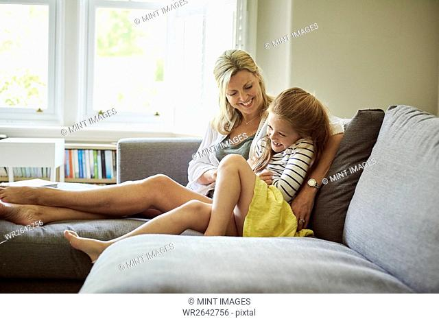 A woman and a child seated on the sofa laughing