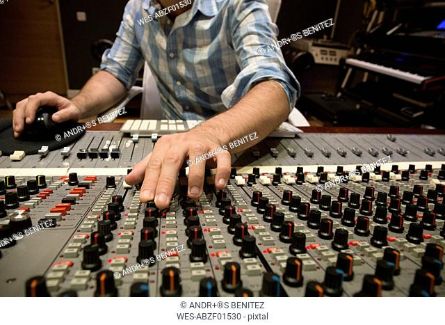 Hand of a man working in the control room of a recording studio