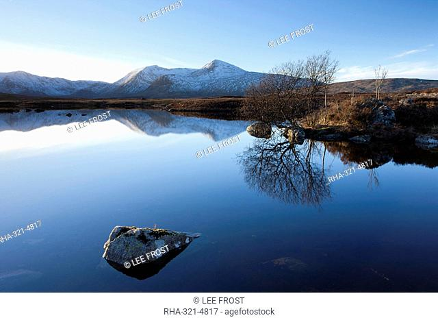Dusk view of snow-covered Black Mount Hills and their reflection in the flat calm Lochain na h'Achlaise, Rannoch Moor, Highland, Scotland, United Kingdom